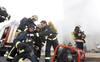 Bomberos luchando con un fuego simulado